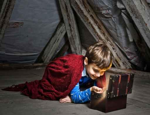 Kind betrachtet einen Schatz auf dem Dachboden